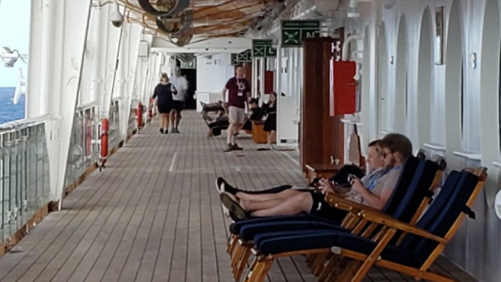 Empty Deck with adults playing on electronics